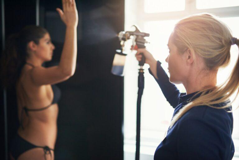 Beautician spraying tan on woman in salon